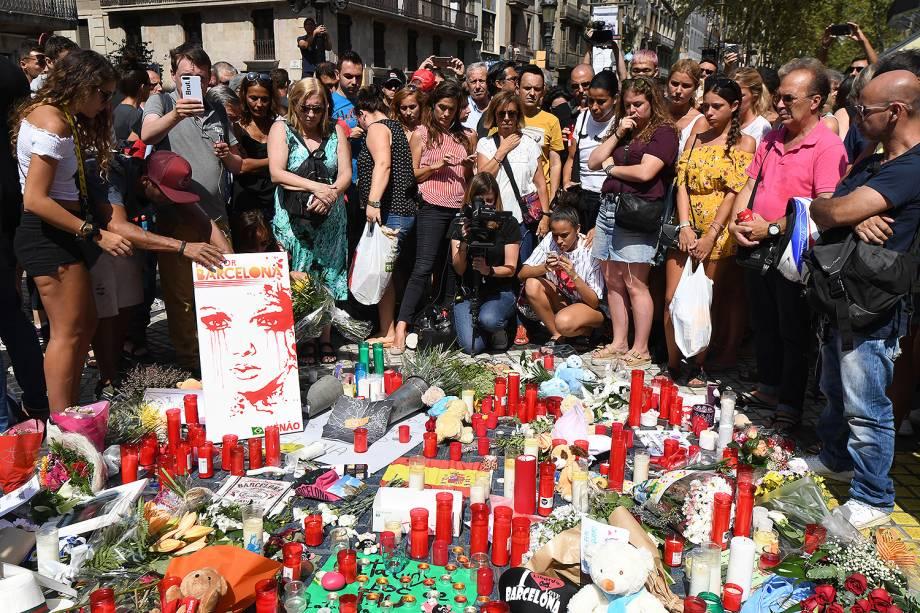 Pessoas levam flores, velas e cartazes para homenagear as vitimas do atropelamento terrorista em La Rambla, Barcelona, na Espanha - 18/08/2017