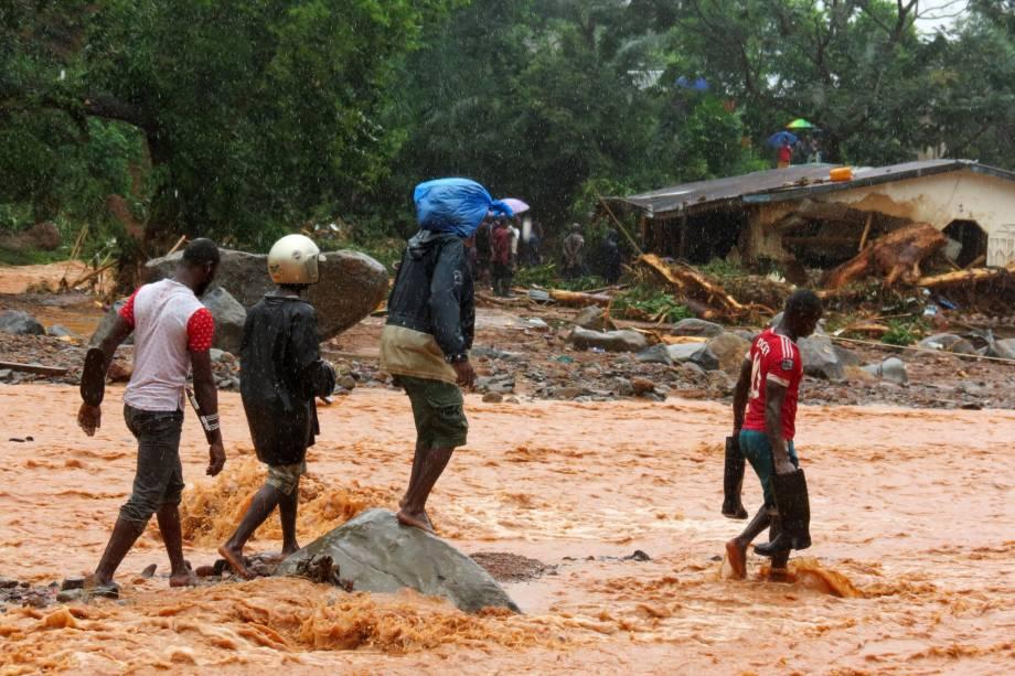 Moradores atravessam uma rua inundada em frente a uma casa em destruída pelas enchentes em Freetown, capital de Serra Leoa - 14/08/2017