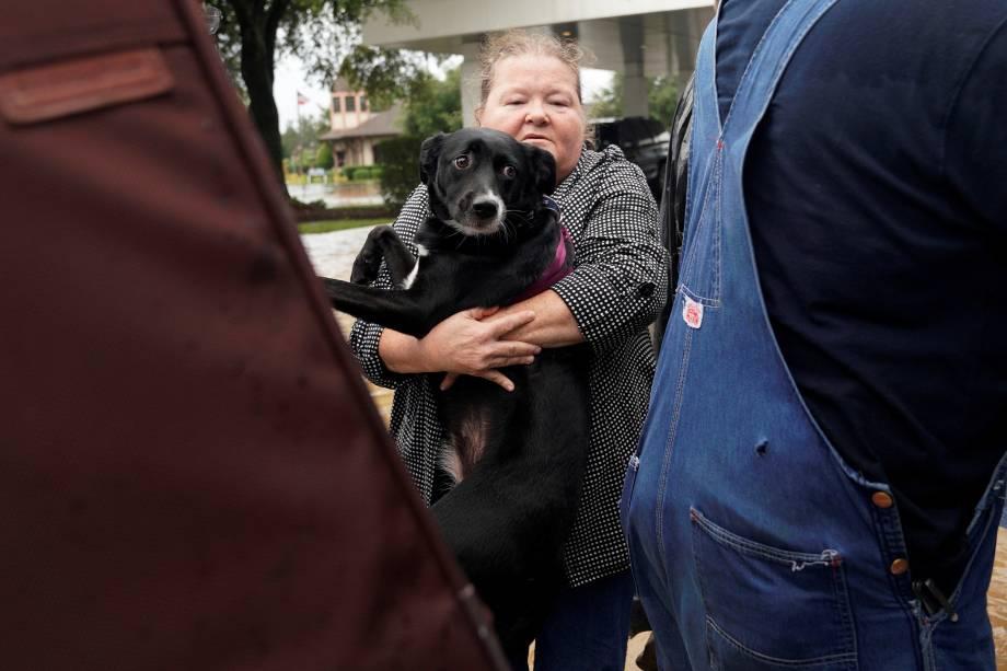 Mulher carrega seu cachorro para um caminhão militar durante evacuação de áreas inundadas após passagem do furacão Harvey em Dickinson, no estado americano do Texas - 27/08/2017