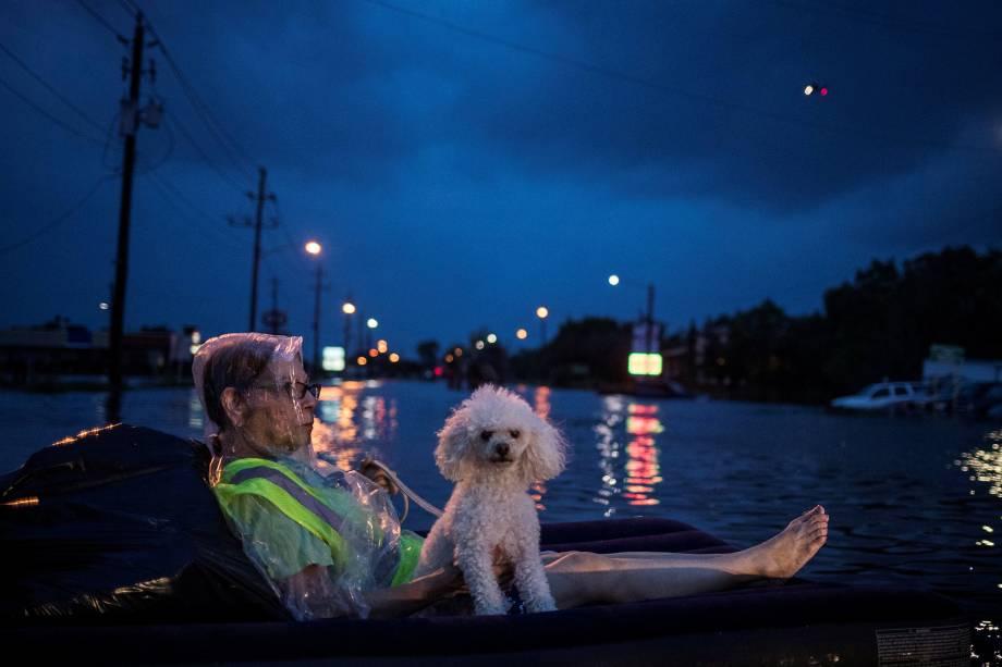 Mulher usa um colchão de ar para flutuar com seu cão acima das águas de inundação provocadas pelo furacão Harvey enquanto espera para ser resgatada em Houston, no estado americano do Texas - 27/08/2017