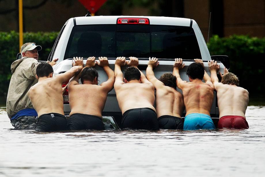 Moradores empurram caminhonete em rua alagada na cidade de Houston, no Texas - 28/07/2017