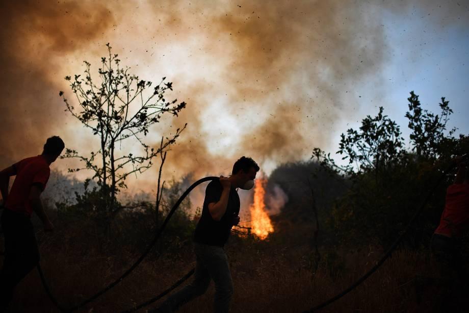 Moradores da vila de Pucarica tentam conter o incêndio que se espalha pela floresta, na cidade de Abrantes, em Portugal