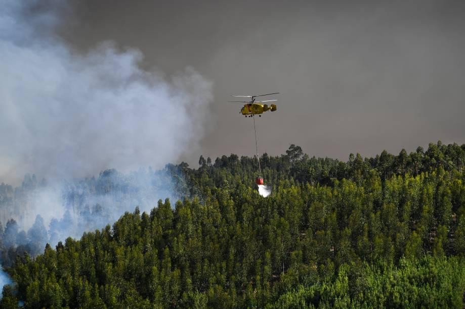 Helicóptero despeja água para conter as chamas do incêndio florestal em Abrantes, Portugal. Cerca de 650 bombeiros apoiados por nove aeronaves e mais de 200 veículos, estavam no local da maior ocorrência