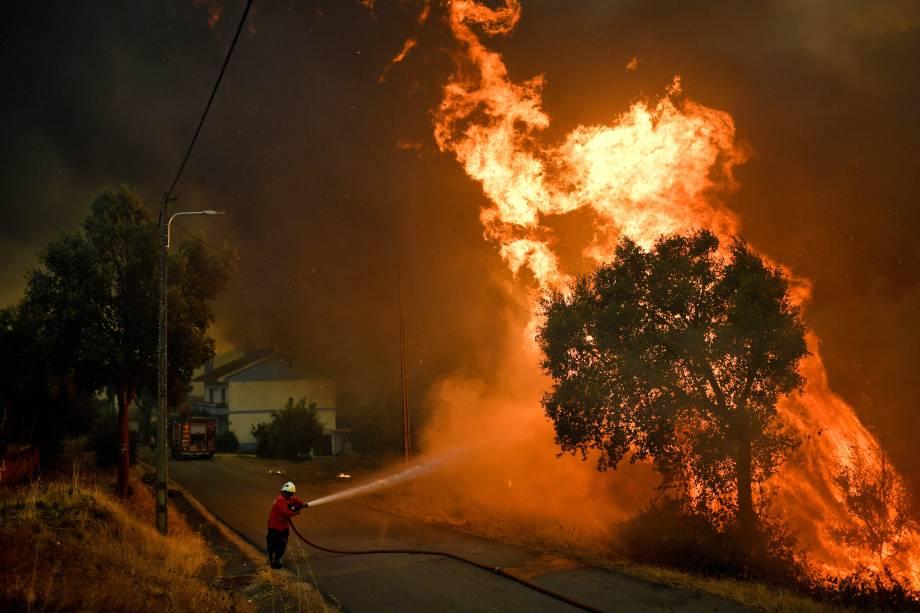 Bombeiro tenta extinguir o fogo do incêndio florestal que atingiu a vila de Pucarica, na cidade de Abrantes, Portugal