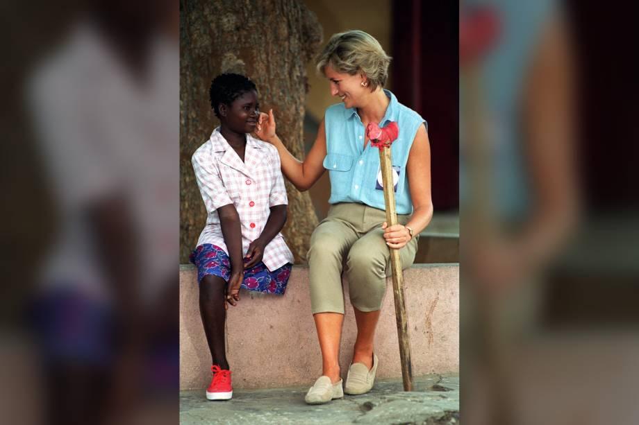 Princesa Diana conversa com a menina Sandra Thijika durante visita a uma oficina ortopédica em Luanda, Angola em janeiro de 1997