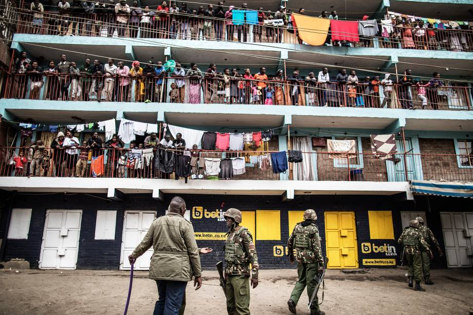 Moradores observam das sacadas enquanto policiais administrativos do Quênia patrulham a região da favela de Mathare, em Nairobi, durante o protesto contra o resultado das eleições gerais