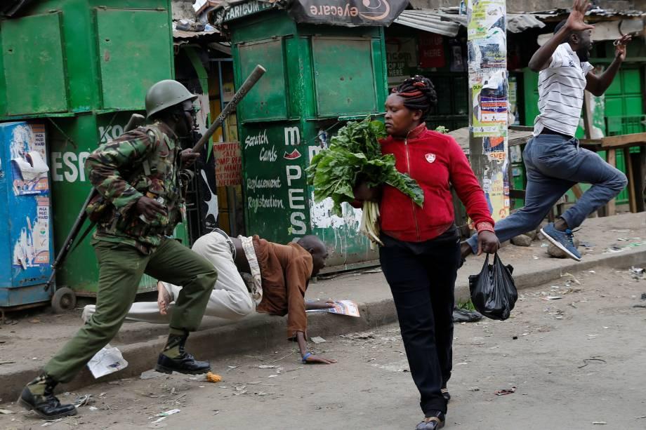 Policiais tentam dispersar manifestantes durante protesto contra o resultado das eleições no Quênia, enquanto uma mulher passa com seus vegetais pelas ruas da favela de Mathare, em Nairobi