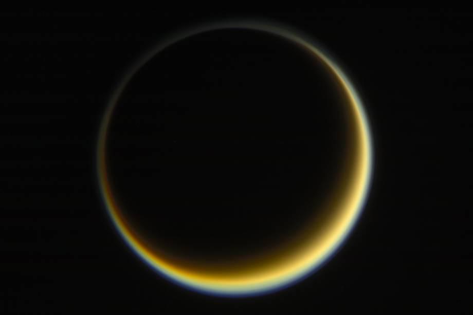 Cassini fotografa face escura de Titã, a maior lua de Saturno, enquanto o Sol ilumina o outro lado. É possível observar a névoa alaranjada que existe na atmosfera do astro.