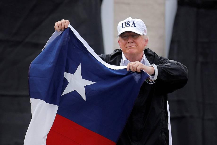 O presidente dos EUA, Donald Trump, segura a bandeira do Texas, na cidade de Corpus Christi, durante visita, após tempestade tropical Harvey, em Corpus Christi
