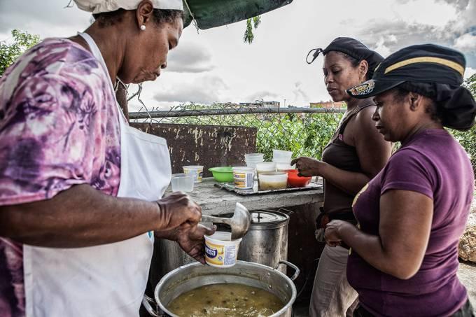 PALIATIVO – Judith Arcia (à esq.) serve sopa feita com carne e legumes doados por cidadãos de classe média, em Caracas: falta comida a preços baixos no país