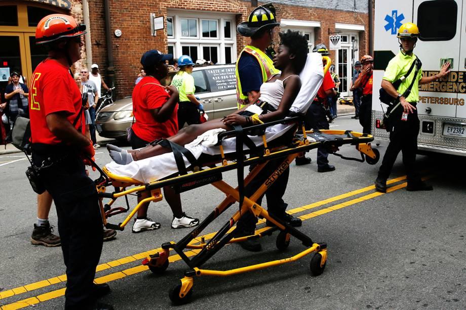 Equipes de resgate levam mulher ferida por um carro que avançou sobre multidão que protestava contra supremacista brancos