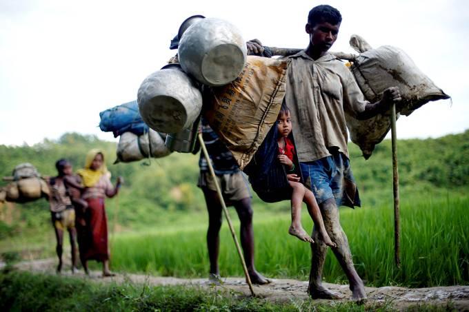 Refugiados rohyngias caminham por uma trilha em um campo de arroz, na travessia entre as fronteiras de Myanmar e Bangladesh – 08/09/2017