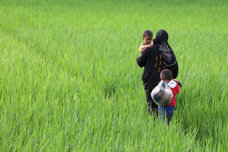 Mulher rohingya caminha com seus filhos por um campo em Bangladesh, após fugir de Myanmar - 10/09/2017