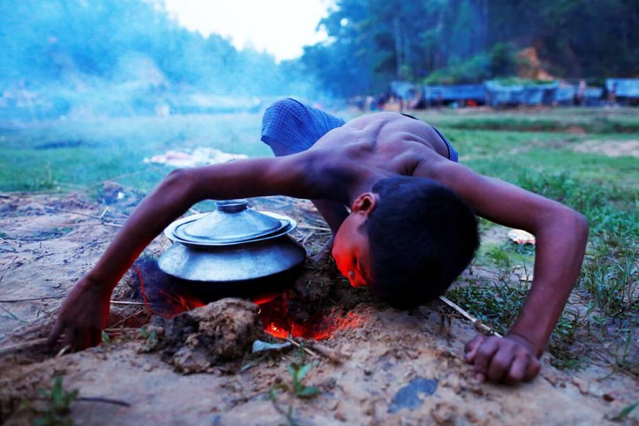Criança refugiada acende fogo para cozinhar uma refeição, próximo ao seu abrigo temporário - 12/09/2017