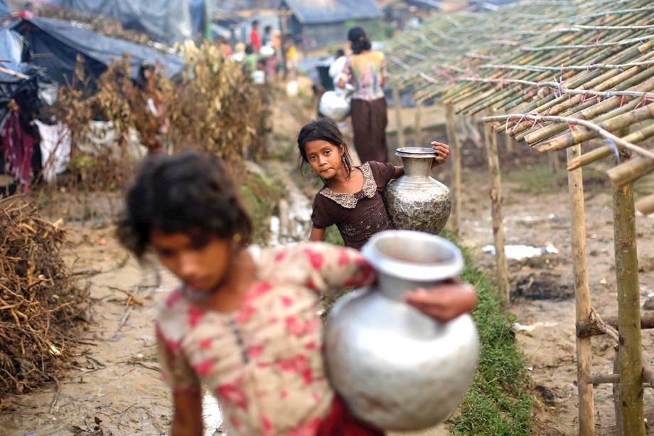 Crianças rohingyas carregam vasos com água em um campo de refugiados, em Bangladesh - 13/09/2017