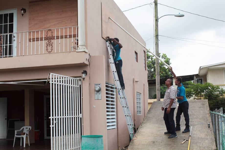 Homens protegem janelas com placas para a chegada do Furacão Irma, em San Juan, Porto Rico
