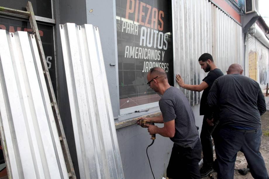 Homens protegem janelas com placas para a chegada do Furacão Irma, em San Juan, Porto Rica