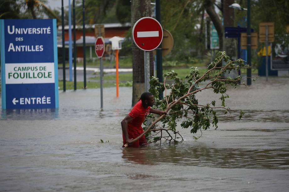 Homem retira um galho de uma via alagada após a passagem do furacão Maria pela cidade de Pointe-à-Pitre, na ilha francesa de Guadalupe, no Caribe - 19/09/2017