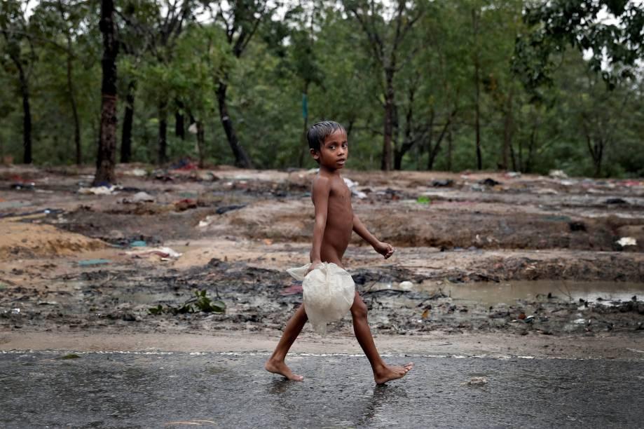 Um garoto rohingya é fotografado andando na chuva pelo acampamento de refugiados Cox' Bazar, em Bangladesh - 20/09/2017
