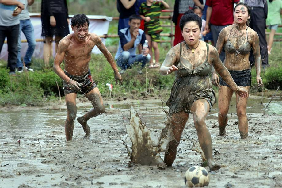 Crianças jogam futebol em um pequeno campo coberto de lama em Jinhua, Zheijang, na China - 25/09/2017
