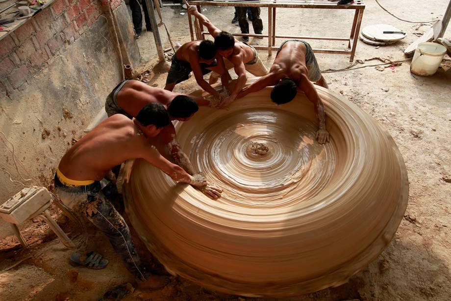Trabalhadores fazem um tonel de porcelana em uma fábrica em Jingdezhen, China - 25/09/2017
