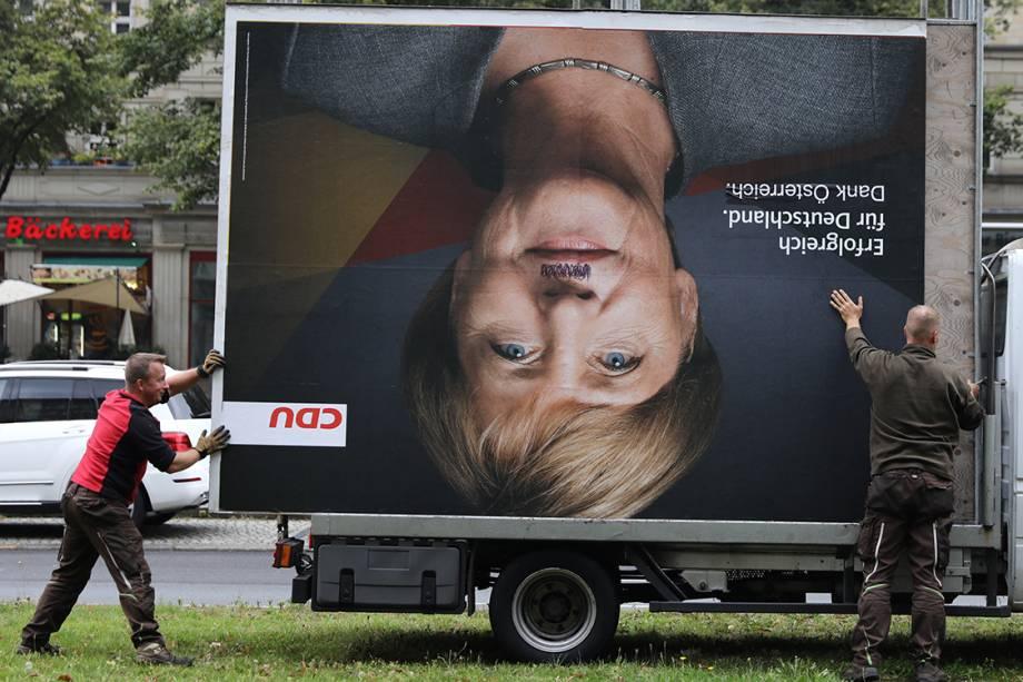 Funcionários removem outdoor de Angela Merkel após vândalos picharem o rosto da Chanceler, em Belim, Alemanha - 25/09/2017