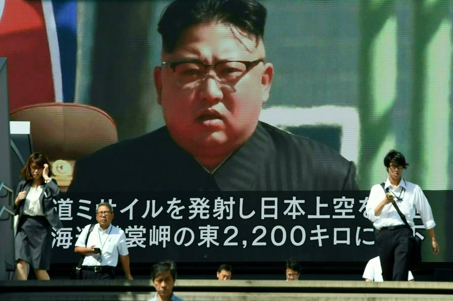 Pedestres caminham em frente a um telão no centro de Tóquio durante transmissão de um telejornal com a imagem do ditador norte-coreano Kim Jong-Un, após a realização de mais um teste de mísseis que passou sobre o território japonês - 15/09/2017