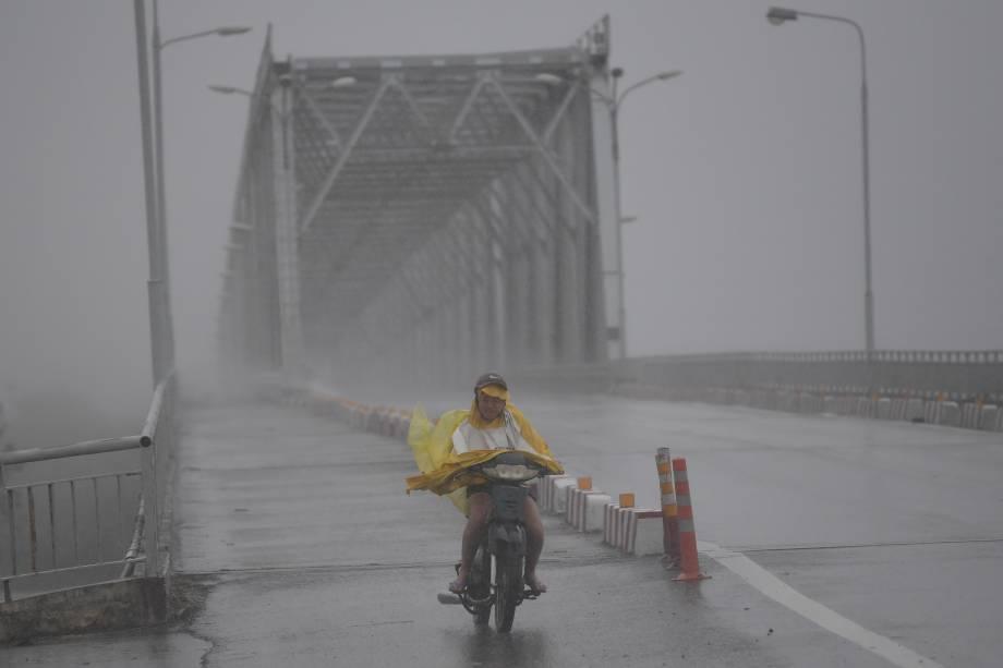Mulher em uma moto atravessa uma ponte durante tempestade provocada pelo tufão Doksuri na província central de Ha Tinh, na costa central do Vietnã - 15/09/2017
