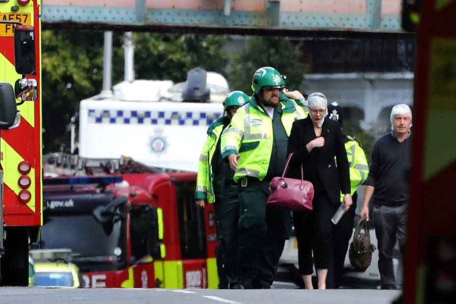 Uma mulher e um homem feridos na explosão de uma bomba caseira no metrô são conduzidos pela equipe de emergência, para fora da estação de Parsons Green, em Londres - 15/09/2017