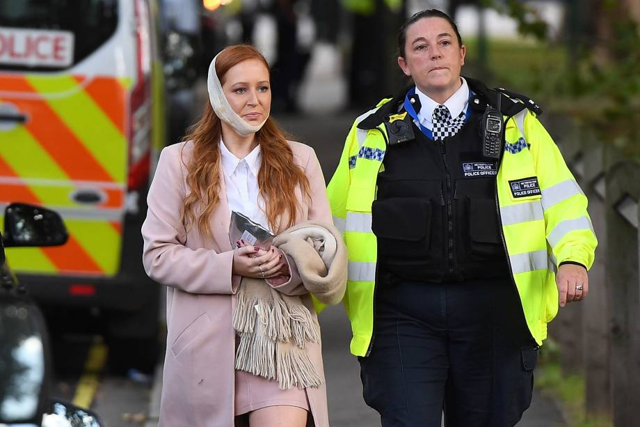 """Policial acompanha uma mulher ferida após uma bomba caseira explodir dentro do vagão de um trem na Estação Parsons Green, da District Line, conhecida como """"linha verde"""" em Londres. A polícia trata o caso como terrorismo - 15/09/2017"""