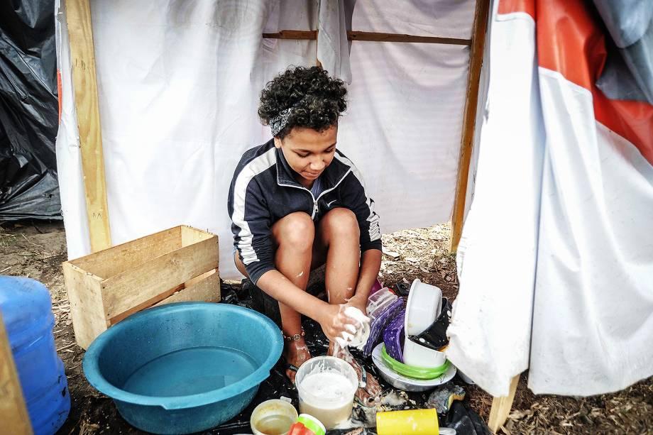 Menina lava louça em ocupação do Movimento dos Trabalhadores Sem Teto (MTST) em um terreno em São Bernardo do Campo