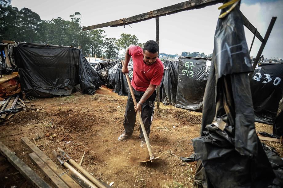 Miliante prepara terra para construir uma barraca, durante ocupação do MTST em um terreno em São Bernardo do Campo