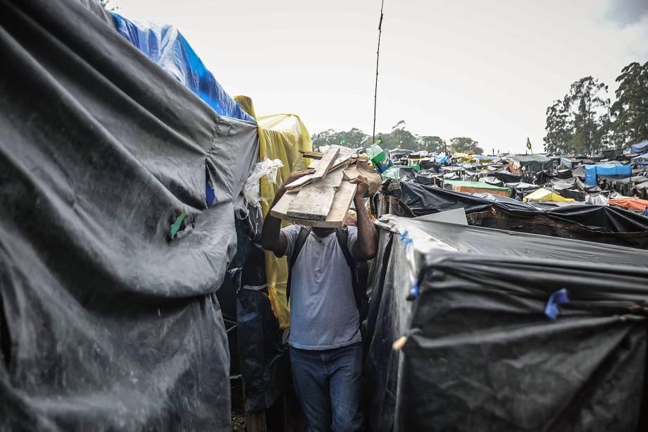 Militante carrega estacas de madeira para construir uma barraca, em ocupação do MTST em um terreno em São Bernardo do Campo