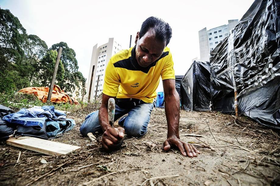 Militante cava buraco para construir uma barraca em ocupação do MTST em um terreno em São Bernardo do Campo