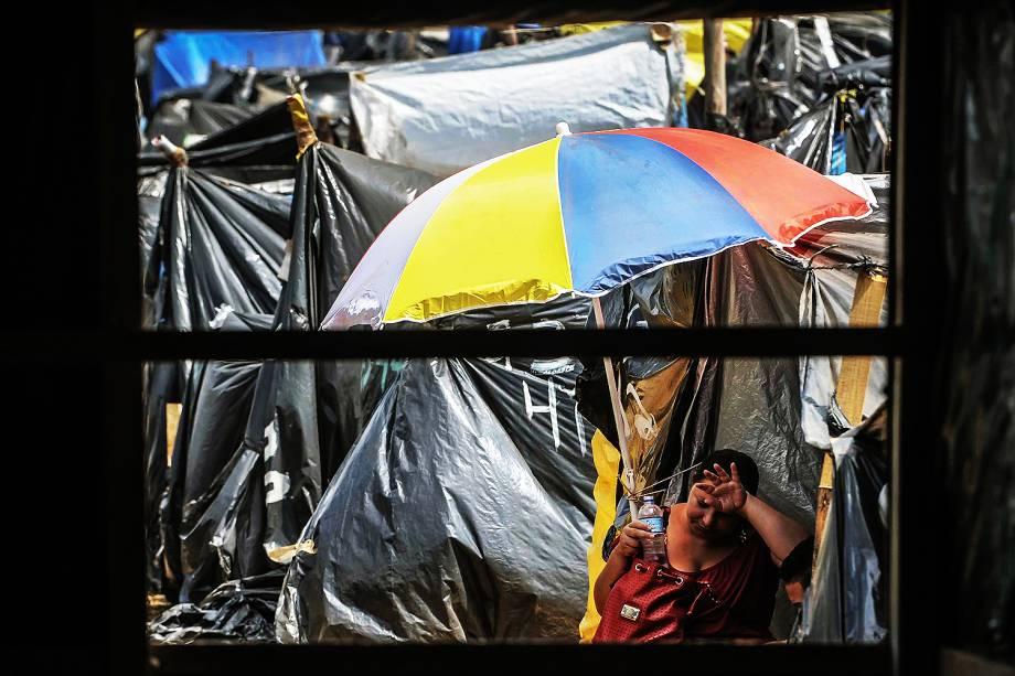 Militante se abriga do calor durante ocupação do MTST em um terreno em São Bernardo do Campo