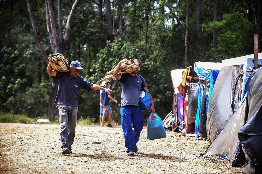 Militantes carregam estacas de madeira para construir barracas, em ocupação do MTST em um terreno em São Bernardo do Campo