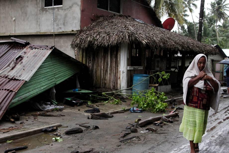 Mulher passa ao lado de uma casa danificada pela passagem do furacão Irma na costa da República Dominicana, em Nagua - 07/09/2017