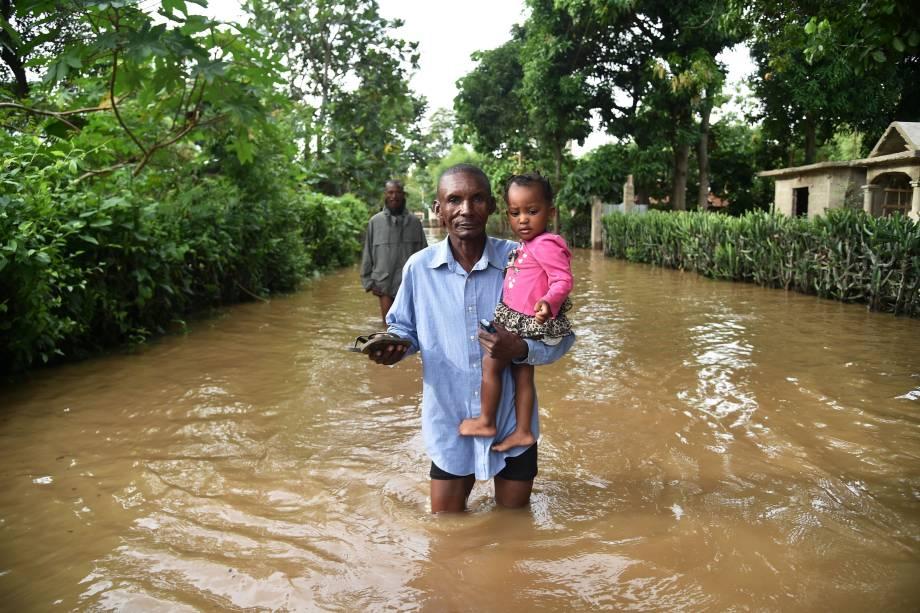 Homem carrega uma criança em uma rua inundada na cidade de Fort Liberte, no nordeste do Haiti durante a passagem do furacão Irma - 08/09/2017