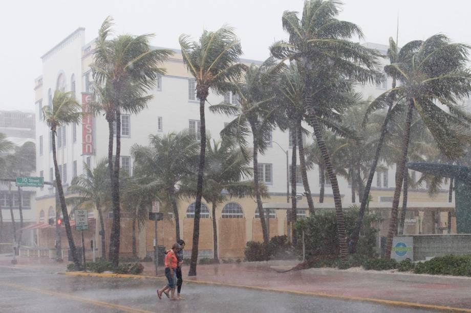 Pessoas caminham pela rua enquanto os ventos e a chuva começam a bater com a aproximação do furacão Irma em Miami Beach, Flórida (EUA) - 09/09/2017