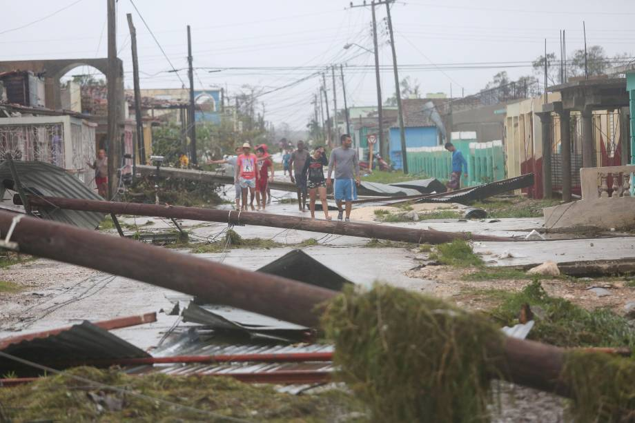 Pessoas caminham em uma rua coberta de destroços após passagem do furacão Irma em Caibarien, em Cuba - 09/09/2017