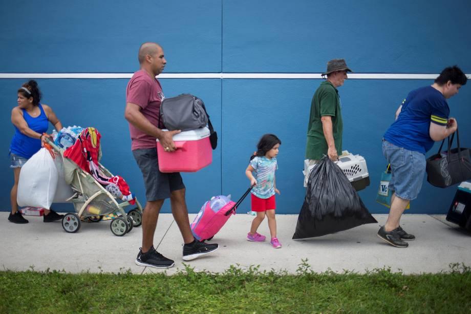 Moradores carregam seus pertences enquanto se dirigem a um abrigo antes da chegada do furacão Irma em Estero na Flórida - 09/09/2017