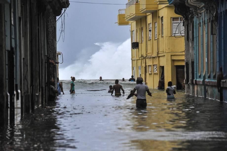 Moradores atravessam uma rua inundada perto do Malecón em Havana após passagem do furacão Irma em Cuba - 10/09/2017