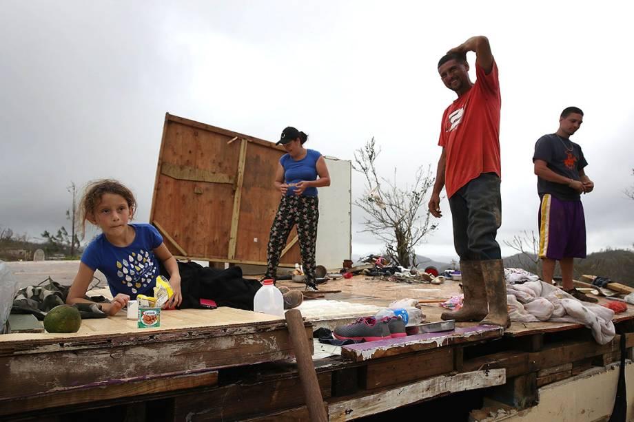 Família desabrigada junta restos de pertences após ter casa destruída pelo furacão Maria, em Hayales de Coamo, Porto Rico