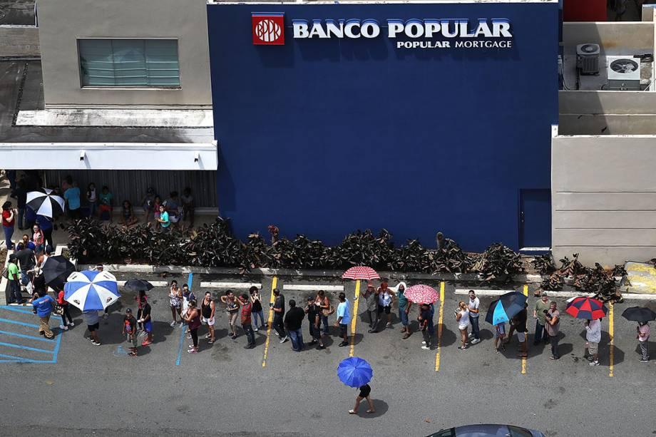 Pessoas aguardam em fila na porta de um banco, após a passagem do furacão Maria, em San Juan, Porto Rico