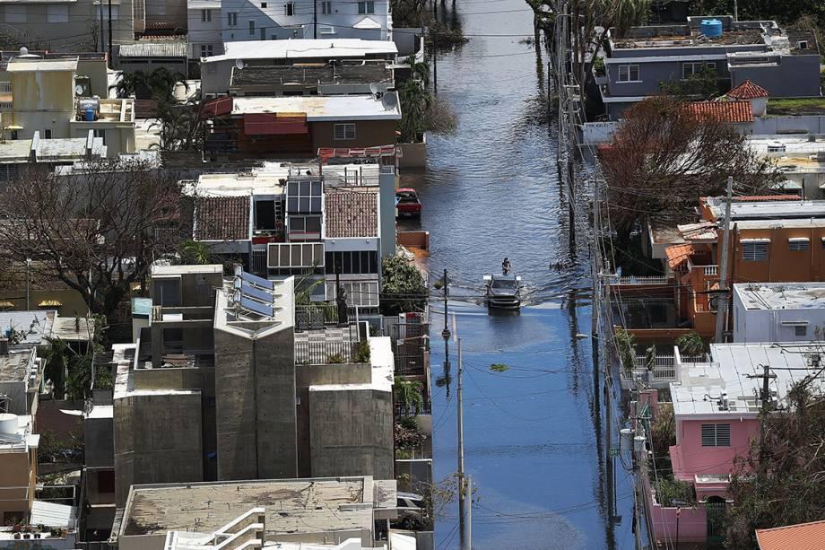 Caminhonete passa por uma rua alagada, após passagem do furacão Maria, em San Juan, Porto Rico