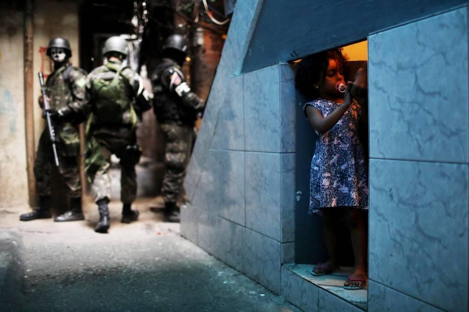 Uma garota é fotografada em uma porta sob uma escada enquanto ao seu redor policiais do Exército patrulham a Favela da Rocinha, durante operação no Rio de janeiro - 25/09/2017