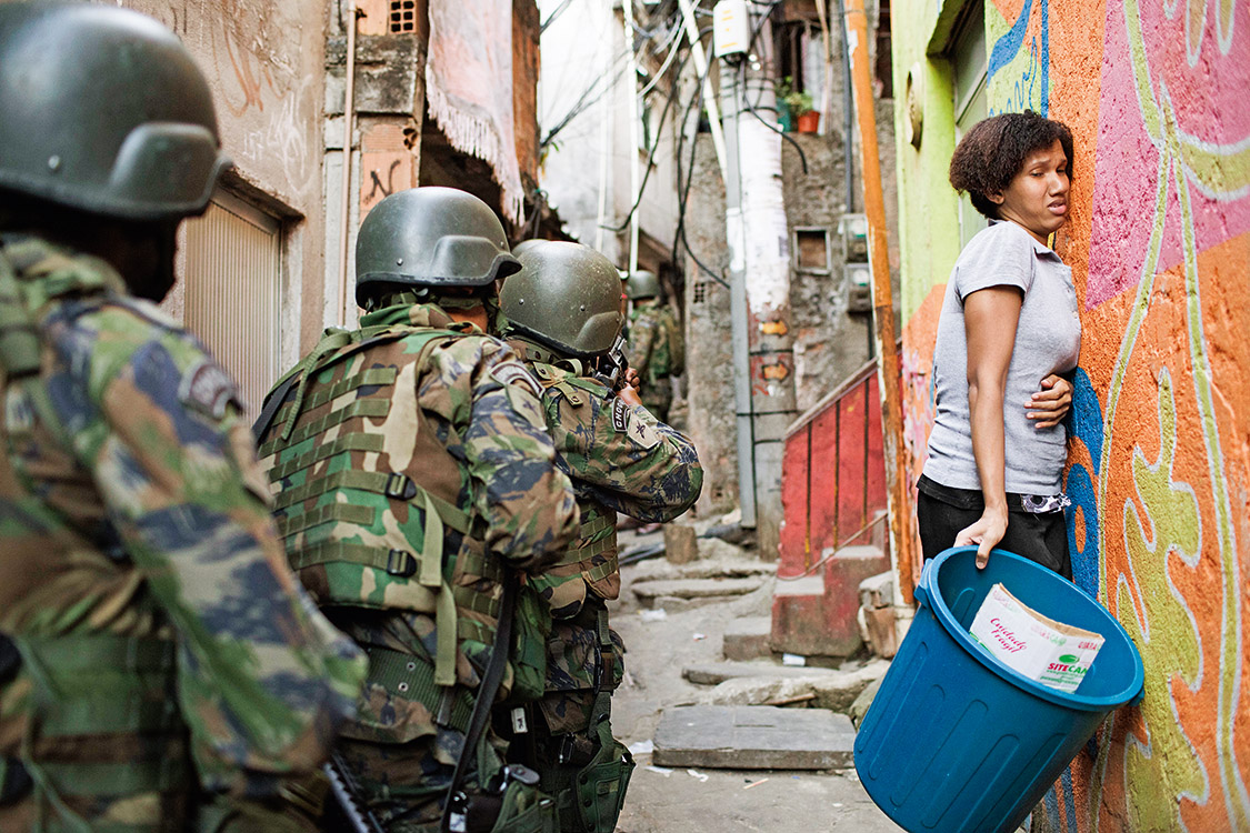 Woman squeezes against the wall as soldiers patrol in an alley during an operation in Rocinha slum in Rio de Janeiro, Brazil, Friday, Sept. 22, 2017. Shootouts erupted in several areas of Rio de Janeiro on Friday, prompting Brazilian authorities to shut roads, close schools and ask for the Army to intervene. (AP Photo/Leo Correa)