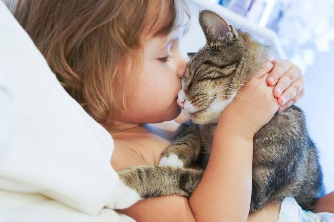 Criança beijando um gato