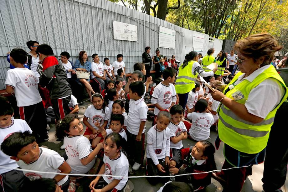 Crianças são reunidas ao longo de uma rua fora da escola, após terremoto atingir a Cidade do México