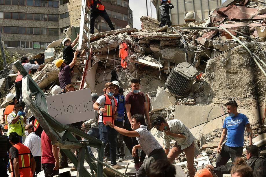 Pessoas mostram um cartaz com o pedido de silêncio, na tentativa de encontrar sobreviventes após terremoto que atingiu o México - 20/09/2017